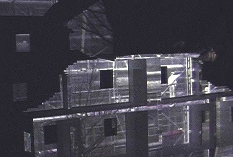 projection of workers on a building, nighttime