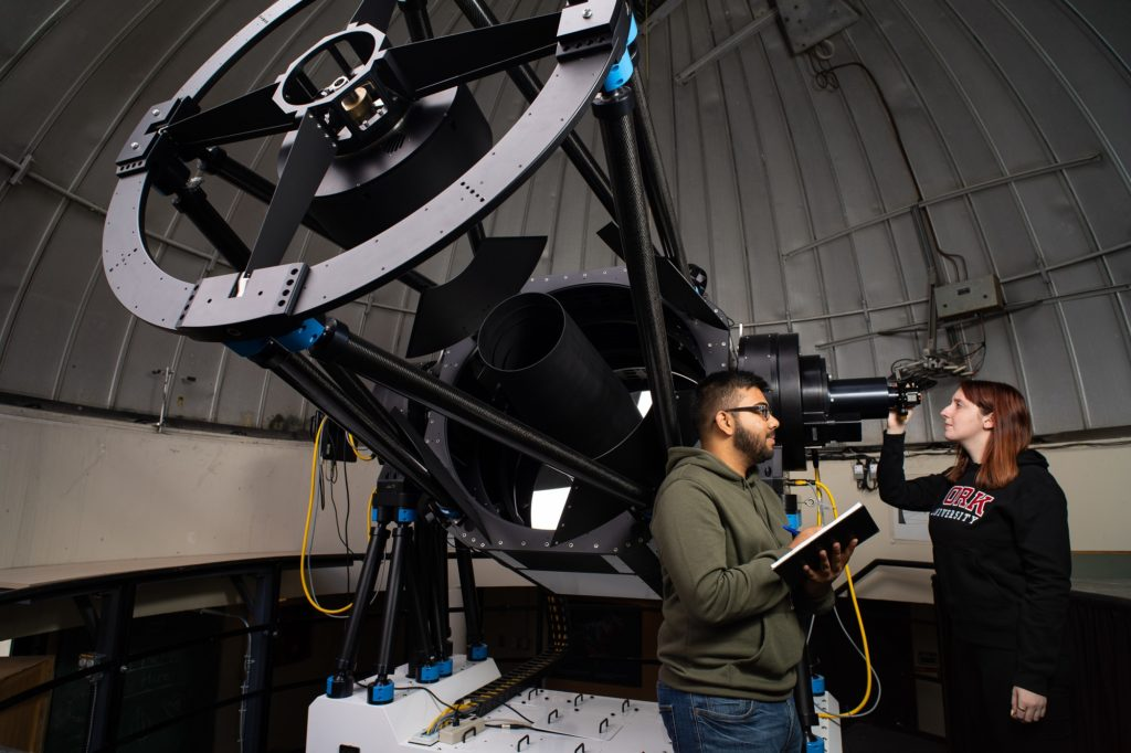 two students working by a telescope