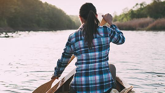 A woman paddles a canoe on a freshwater lake