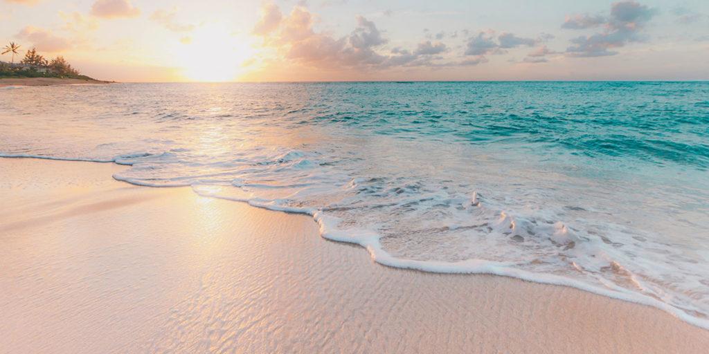 Sun setting over waves on a tropical beach