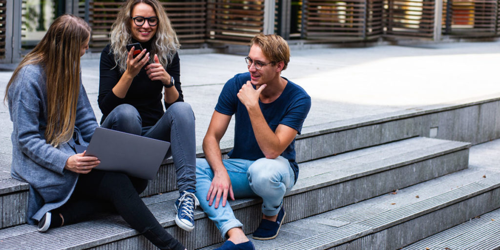 Group of young adults sitting on outdoor concrete steps looking at a laptop screen.