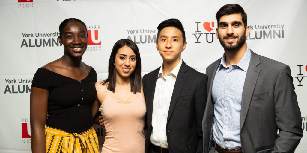 A group of young York University alumni pose in front of a York University alumni backdrop at an event