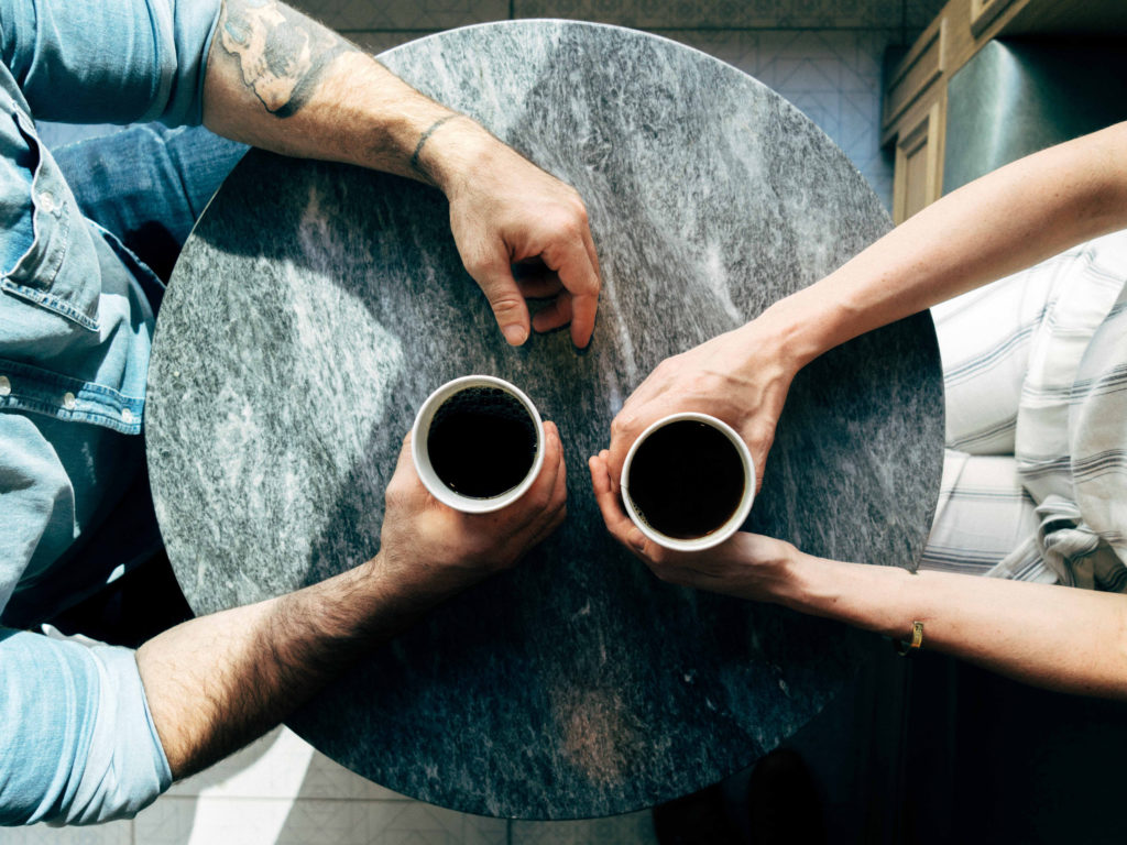 Two people talking and drinking coffee at a cafe table