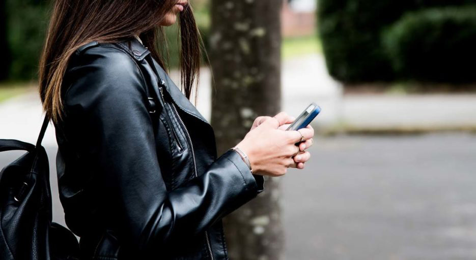 Woman in leather jacket using mobile phone