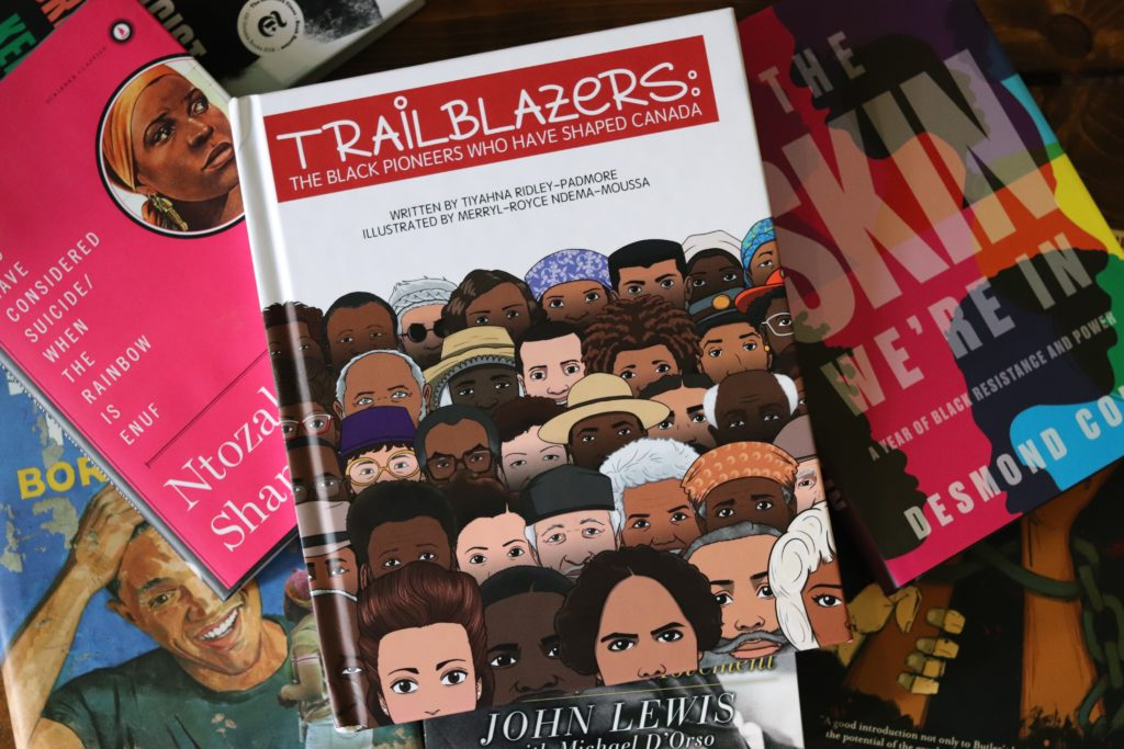 Tiyahna Ridley's new book, Trailblazers: The Black Pioneers Who Have Shaped Canada, sits on top of a pile of other books by Black authors.