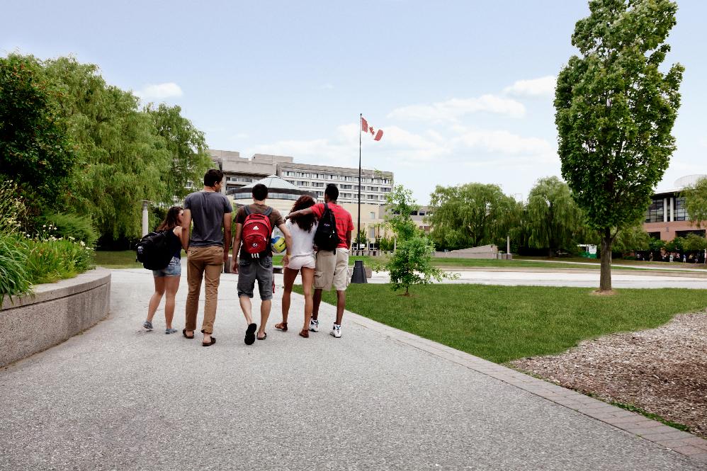 Five students walk down a path on York's Keele campus towards Vari Hall.