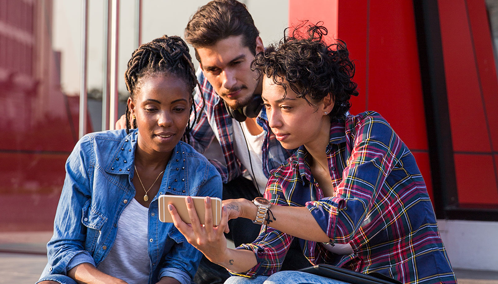 Three racially diverse young adults gathered around a mobile phone screen