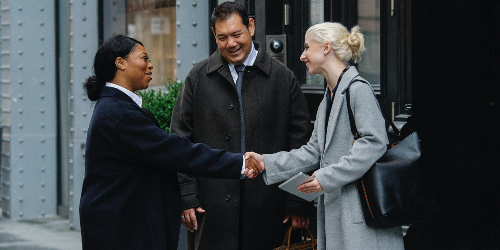 Two women meeting and shaking hands with a man standing between them