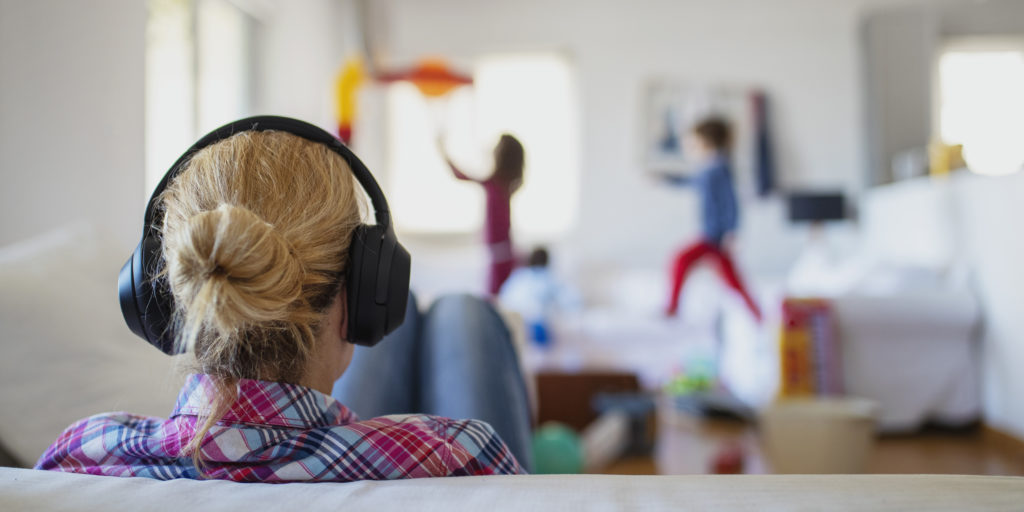 Mother wearing headphones while her kids playing around