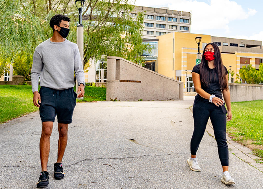 Two students wearing facemasks walk down the path in front of Vari Hall