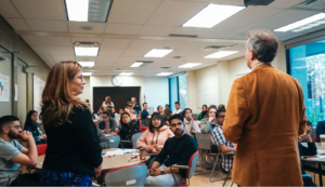 two professors speaking to a group of students in a classroom