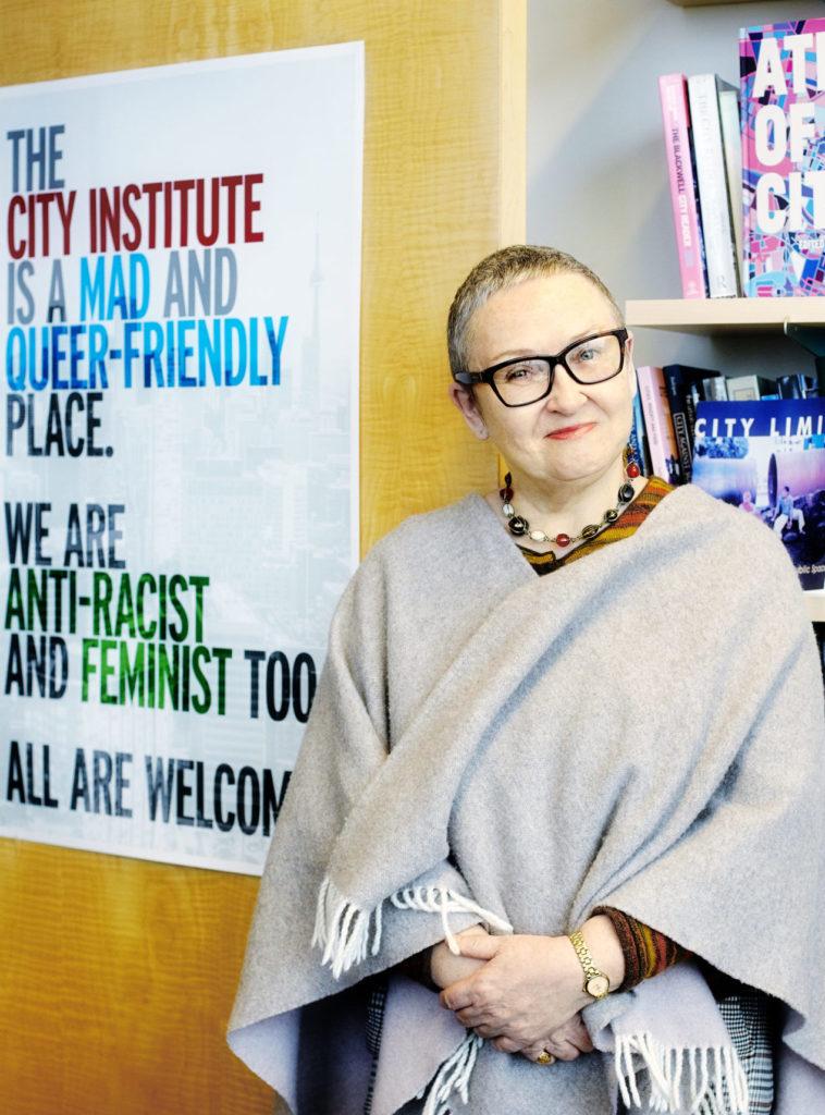 Linda Peake in front of bookshelf and posterposter
