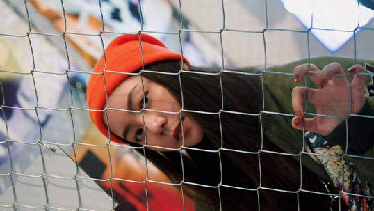 Young woman peeks through fence while wearing orange toque