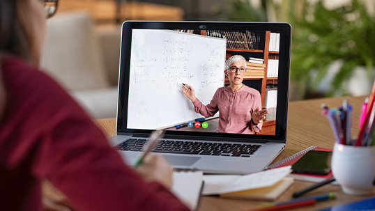 student on computer watching professor
