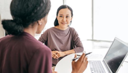 two women in conversation around desk