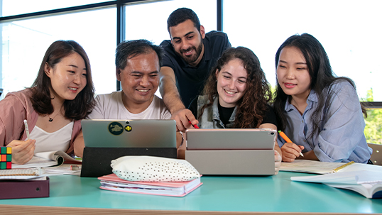 four students and their mentor around a laptop