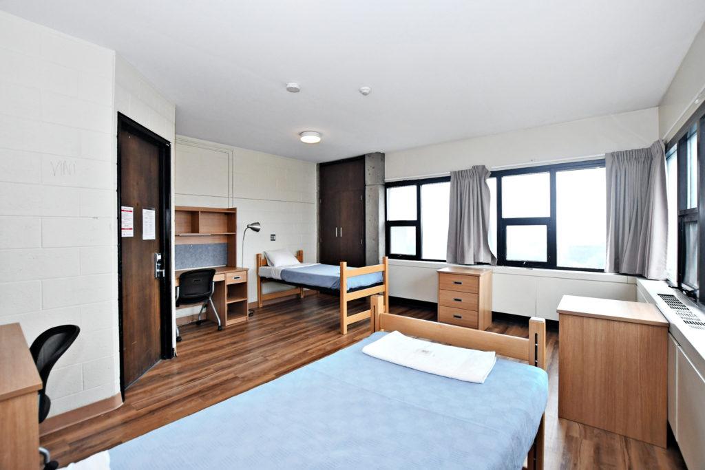 A dorm double room showing beds, desks, dressers, windows.