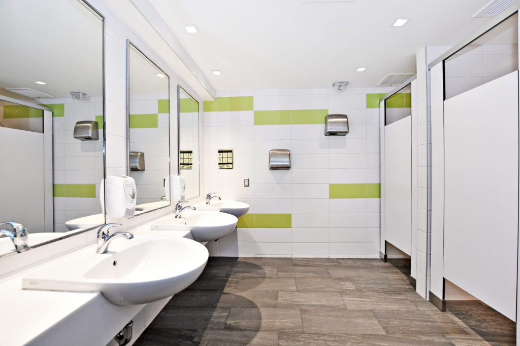 A shared washroom showing three sinks and two stalls.