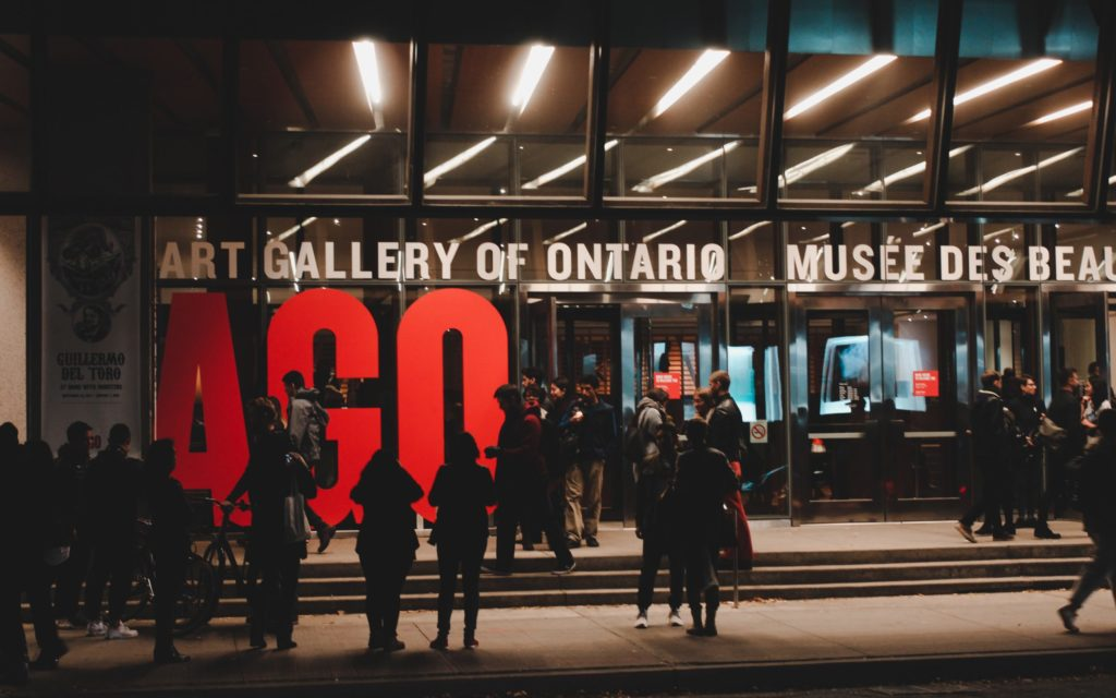 People stand on a sidewalk outside the AGO entrance