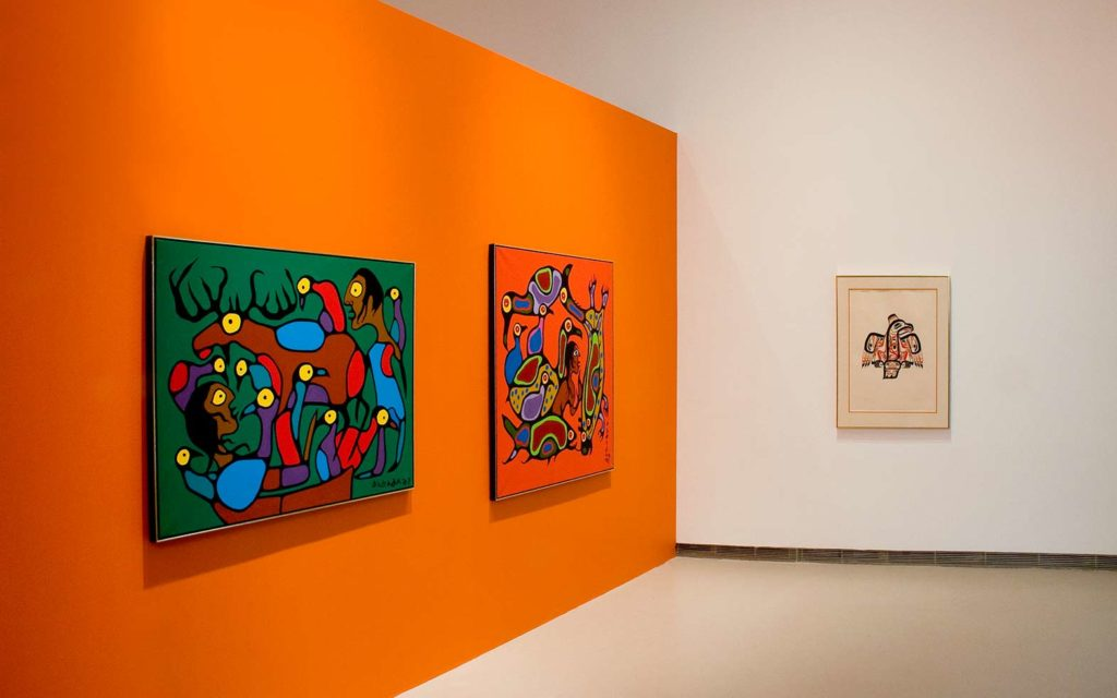 Art pieces hang on an orange wall in a gallery.
