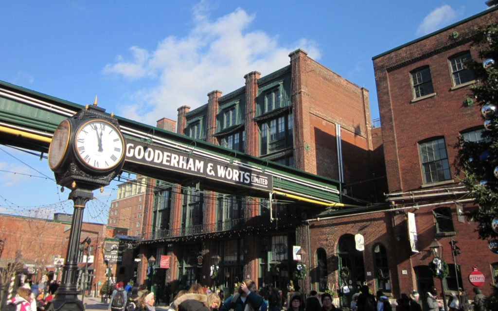 Crowd of people in front of red brick buildings and sign reading Gooderham and Warts Limited