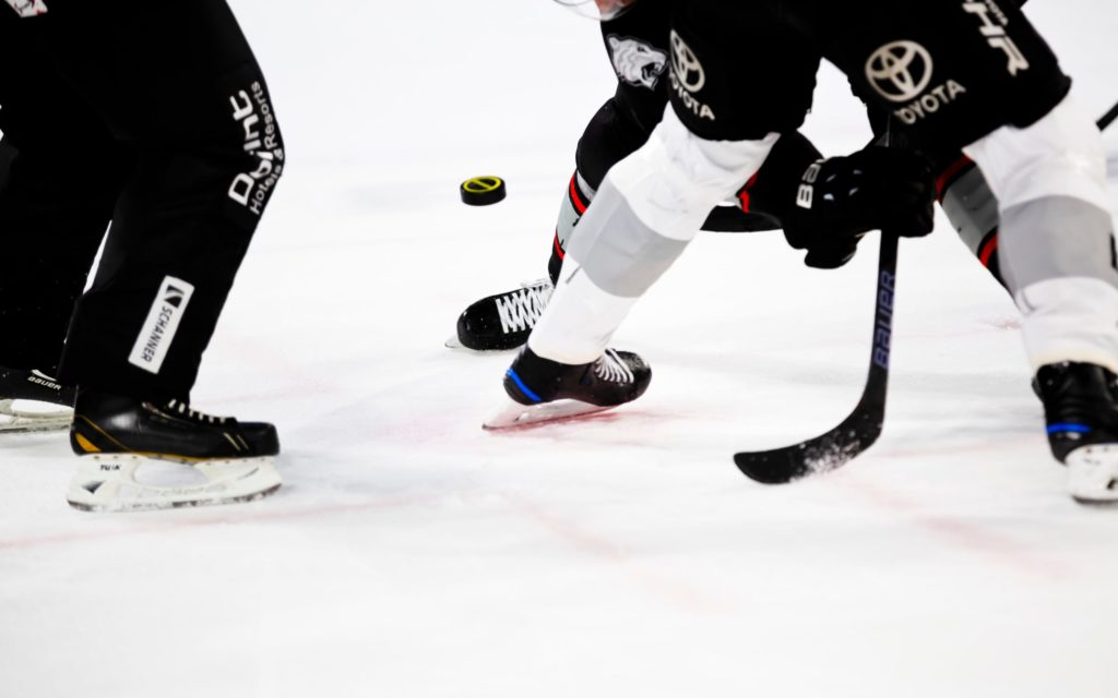 People playing hockey, focused on legs, stick, and puck