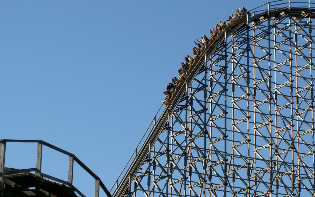 Passengers ride rollercoaster in front of blue sky
