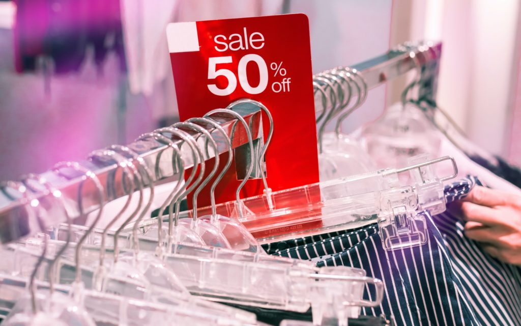 50% off sale sign on a rack of clothing