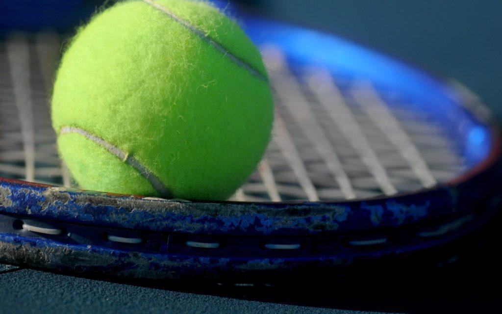 Green tennis ball resting on tennis racket in closeup
