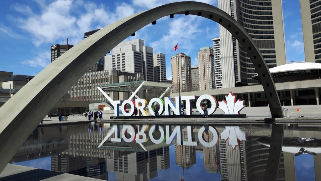 Toronto sign amid concrete buildings and structures against blue sky