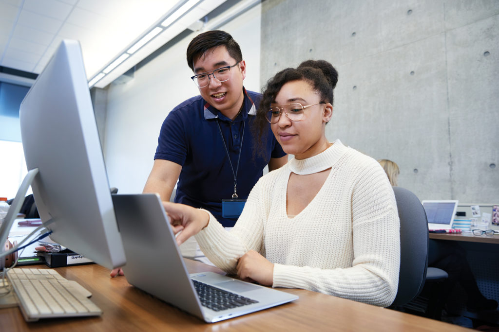 Two students looking at a computer monitor and a laptop screen