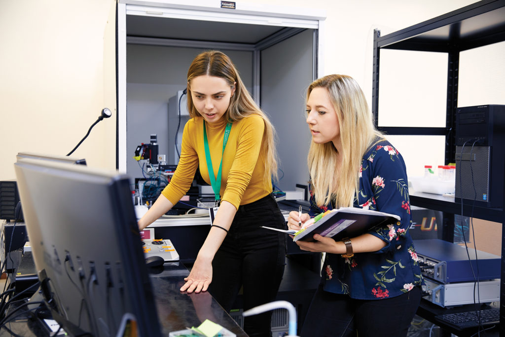 Two students looking at a computer monitor