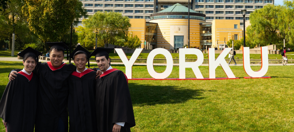 Four York students in grad gowns posing in front of York letters