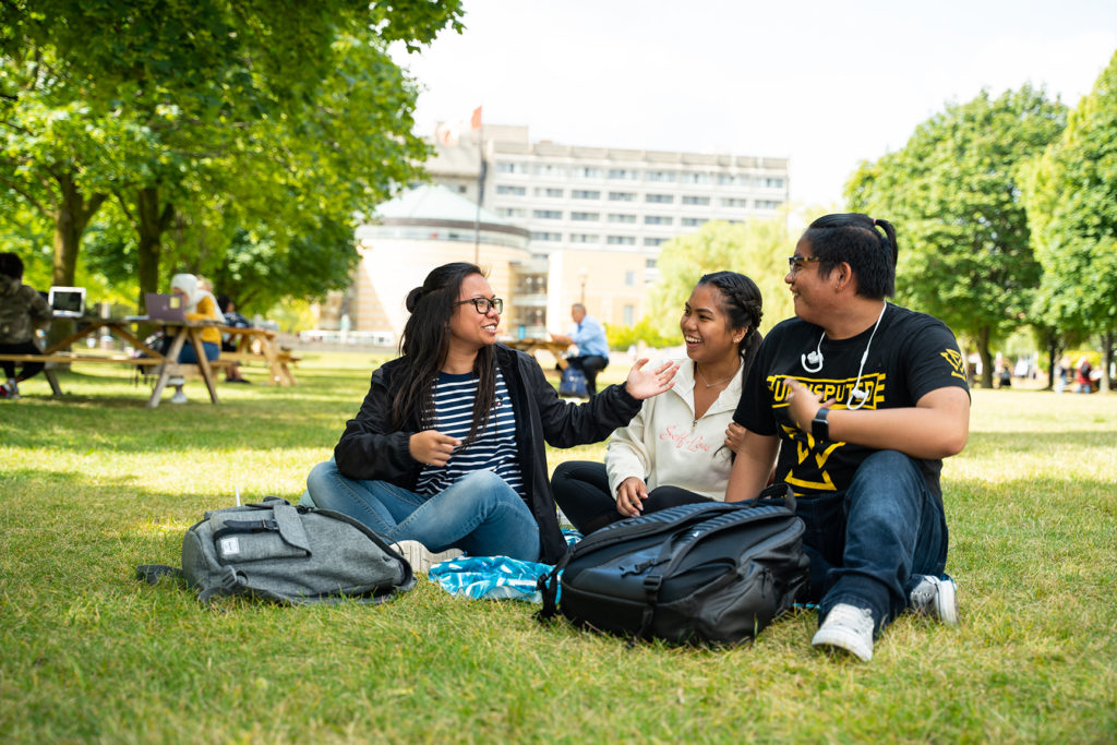 Three students sitting on the grass and talking
