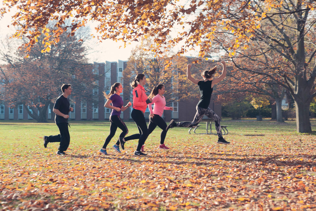 A groups of students running under a tree in the fall
