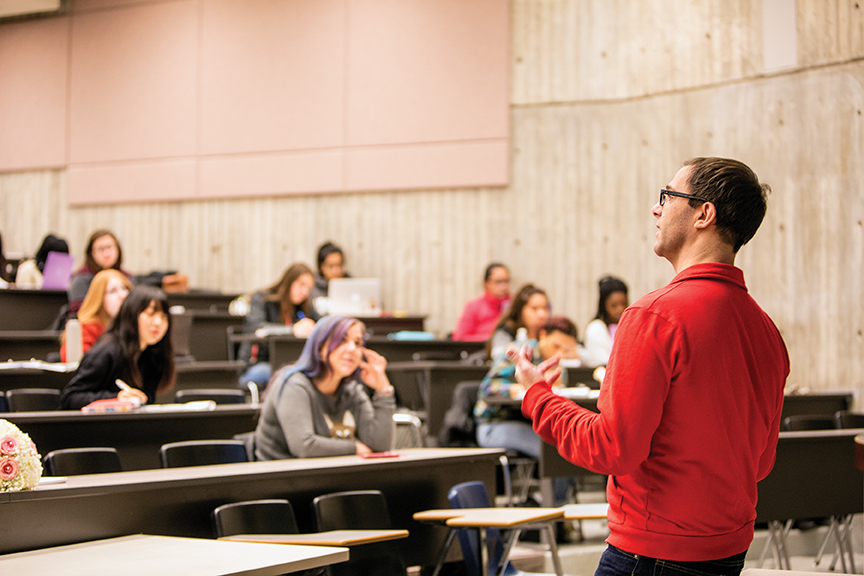 A professor addressing students in a lecture hall