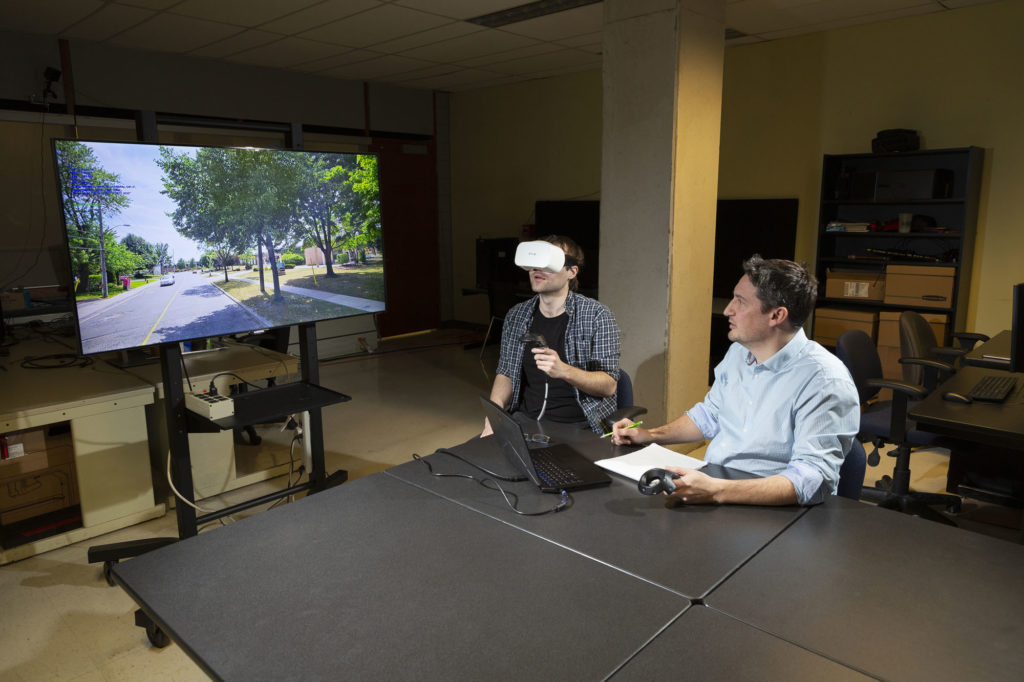Person wearing a VR headset at a table with someone else who is looking at TV displaying the VR images.