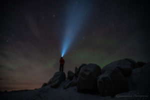 Person with flashlight stands in dark in front of Northern Lights