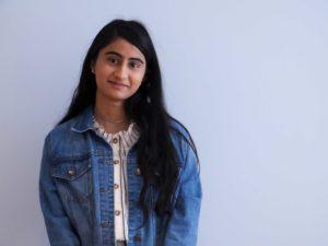 A headshot of Mariya Shireen in front of a blank wall