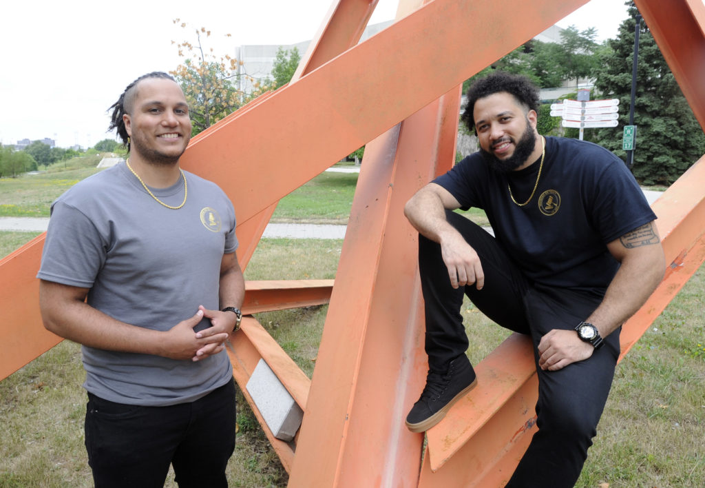 Jonatan Fuentes (left) and his brother, Ryan Fuentes (right) outside in a park posing in front of a large metal abstract art structure.
