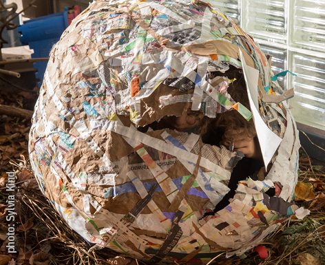 Large paper mache egg with 2 children hiding inside of it