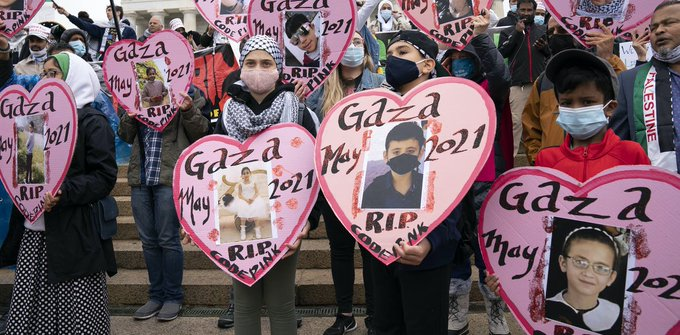 Photographs of children killed in Gaza after Israeli strikes are held by demonstrators during a National March for Palestine in Washington, May 29. 2021. (AP Photo/Jose Luis Magana)