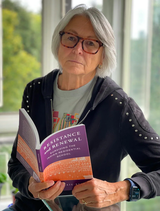 Professor Celia Haig Brown sitting holding a copy of her book Resistance and Renewal: Surviving the Indian Residential School