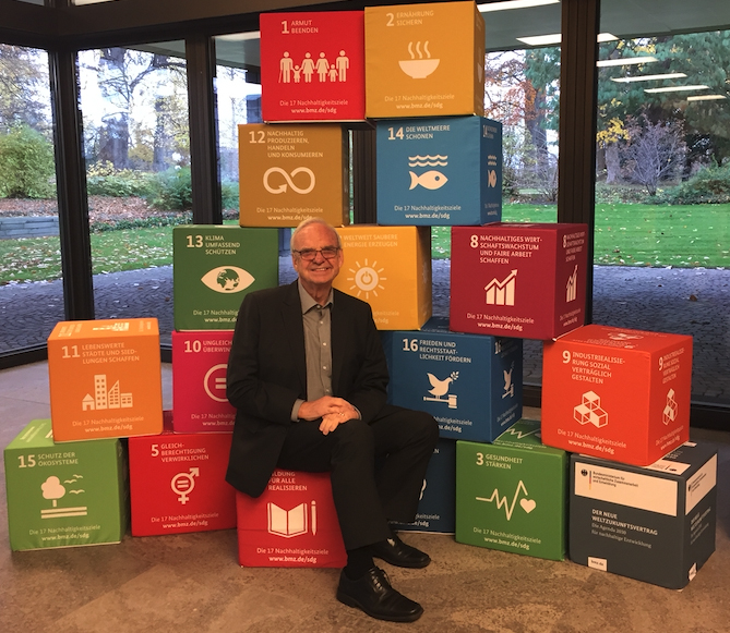 Charles Hopkins sitting in front of a background of blocks displaying each of the United Nations' 17 Sustainable Development Goals