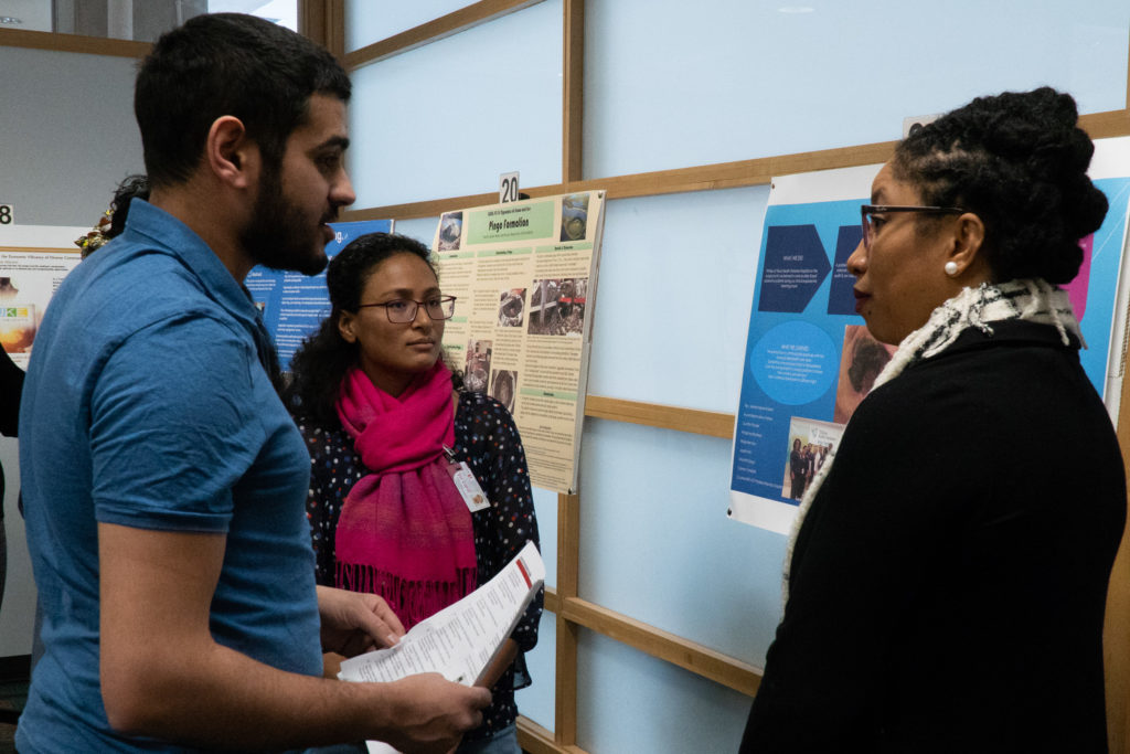 Students listening to a poster presentation