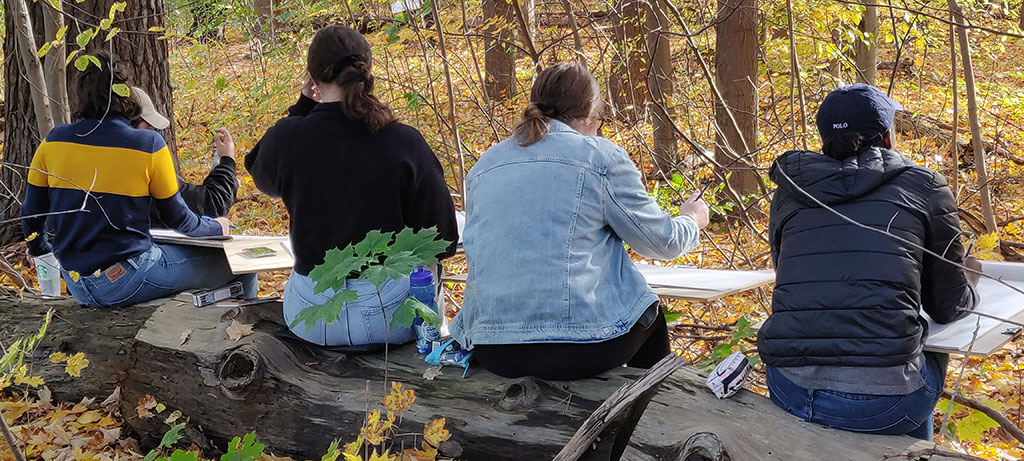 A group of students sketch in the woods.