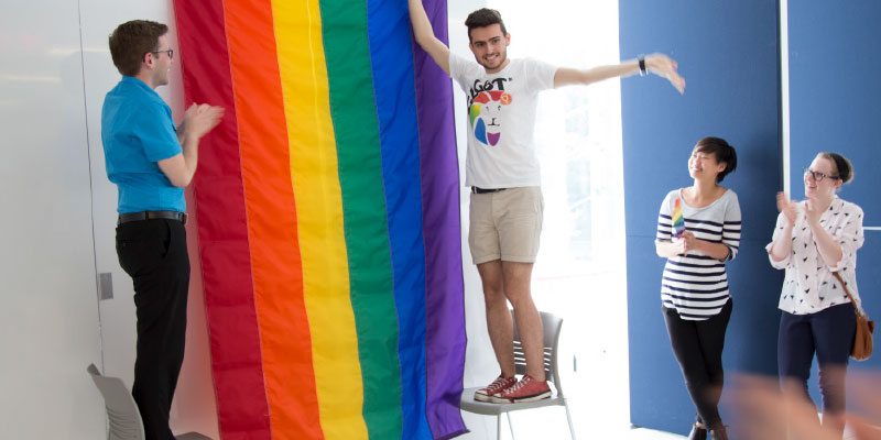 Students hanging a Pride flag.