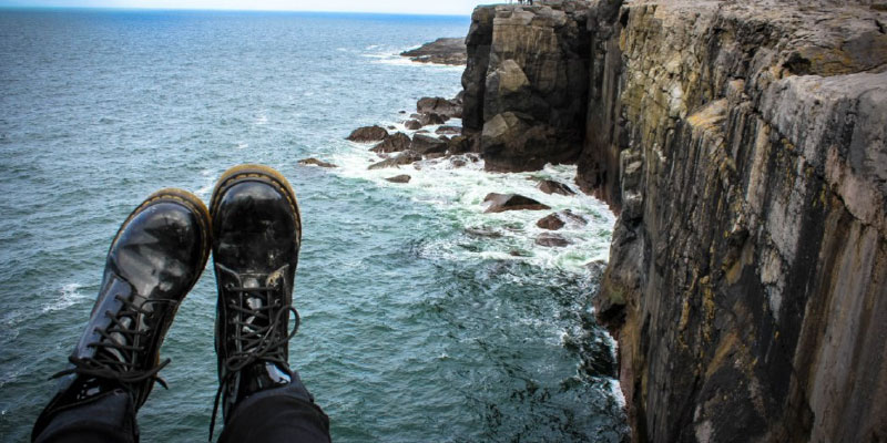 A pair of feet are shown hanging over cliffs on the ocean.