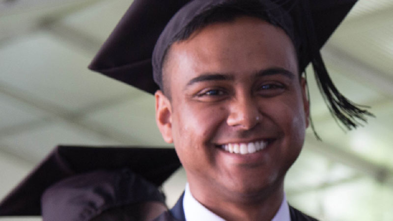 A male graduate smiling.