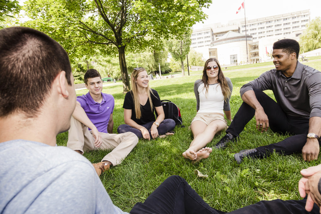 Students sitting on grass with Vari Hall in the background